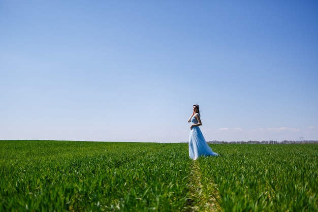 Jonge vrouw in een blauwe lange jurk op een achtergrond van groen veld. modeportret van een mooi meisje met een glimlach op haar gezicht