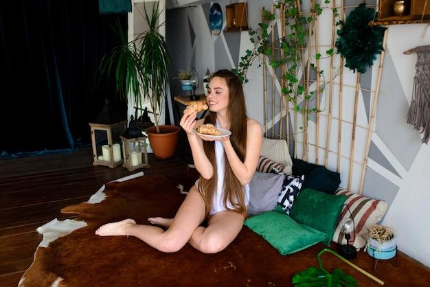 Jonge vrouw in een bodysuit croissants eten