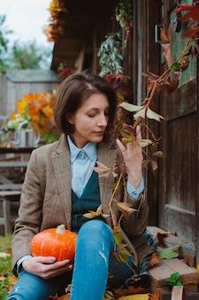 Jonge vrouw in een bruine warme jas en spijkerbroek op een rustieke achtergrond.