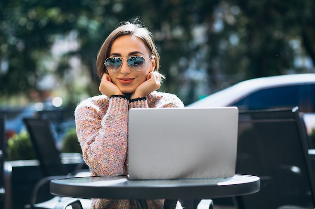 Jonge vrouw in een café met behulp van laptop