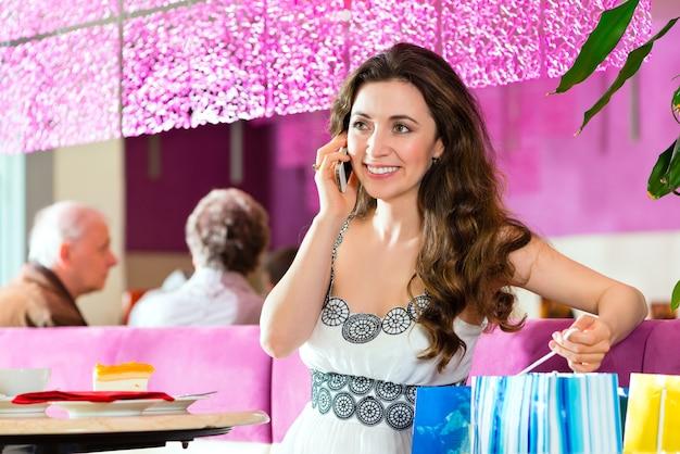 Jonge vrouw in een café of ijssalon die een cake eet en haar telefoon gebruikt, misschien is ze alleenstaand of wacht ze op iemand