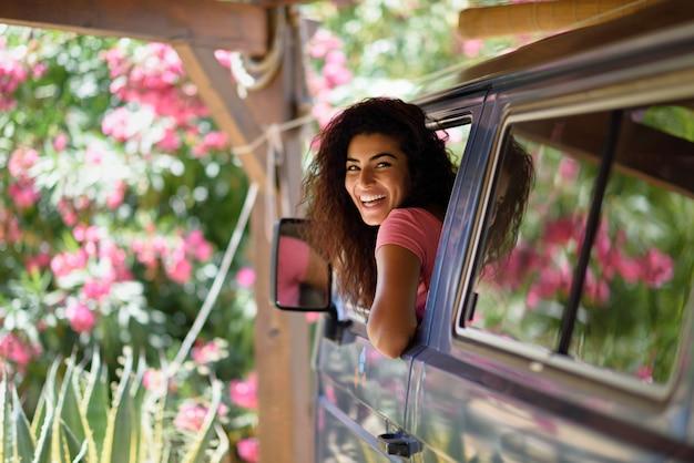 Jonge vrouw in een camper in een mooie camping met roze bloemen