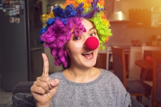 Jonge vrouw in een clownpruik die op vakantie voorbereidingen treffen