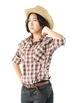 Jonge vrouw in een cowboyhoed en geruite overhemd met hand op haar hoed