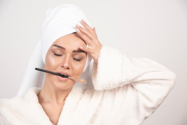 Jonge vrouw in een de samenstellingsborstel van de badjasholding in haar mond.