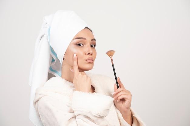 Jonge vrouw in een de samenstellingsborstel van de badjasholding.