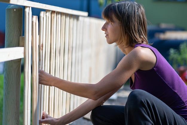Jonge vrouw in een doe-het-zelf-project die buiten een hek van houten planken maakt
