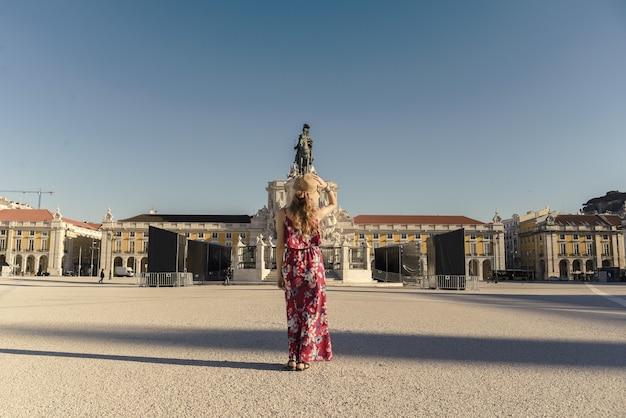 Jonge vrouw in een gebloemde jurk die rondloopt op het commerce square in lissabon, portugal