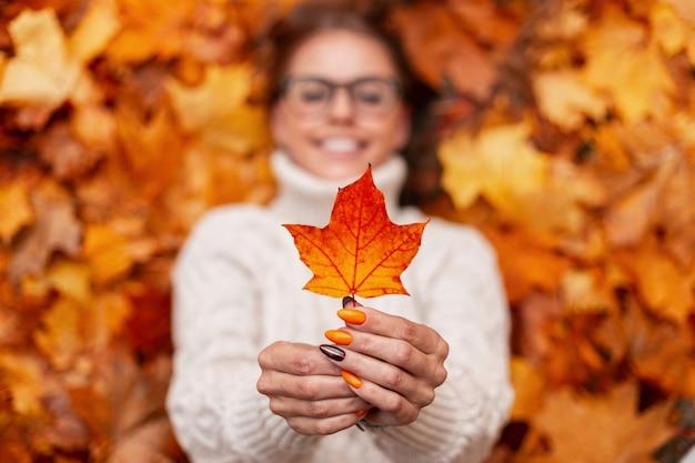 Jonge vrouw in een gebreide trendy witte trui houdt een oranje-gouden herfstblad in handen. vrouw met kleurrijke manicure ligt op de gele bladeren in het park. focus op vrouwelijke handen met een herfstblad.
