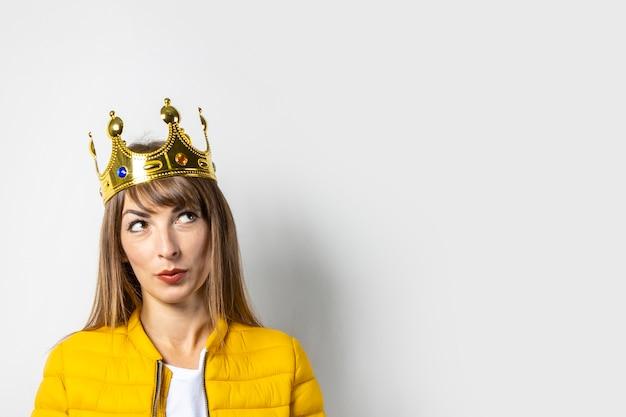 Jonge vrouw in een geel jasje en een gouden geïsoleerde kroon