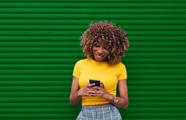Jonge vrouw in een gele blouse die de phone met beide handen houdt
