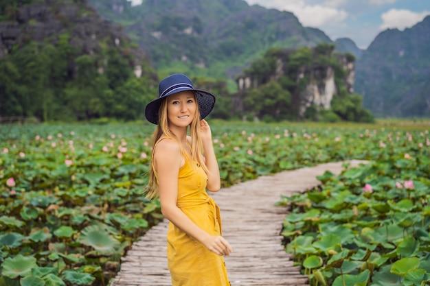 Jonge vrouw in een gele jurk op het pad tussen de lotusmeer mua grot ninh binh vietnam vietnam