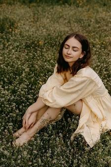 Jonge vrouw in een gele jurk zittend in een veld met wilde bloemen