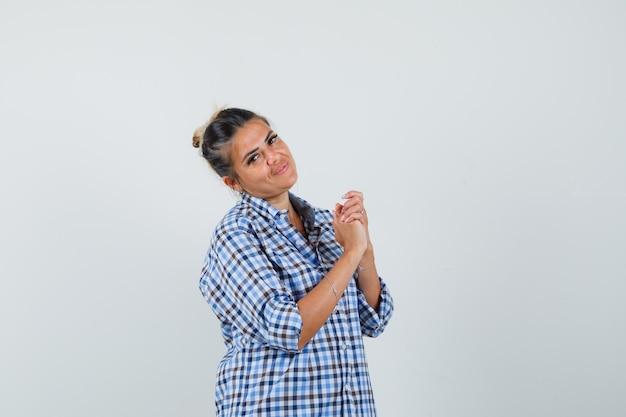Jonge vrouw in een geruit overhemd dat handen combineert en hoopvol kijkt.