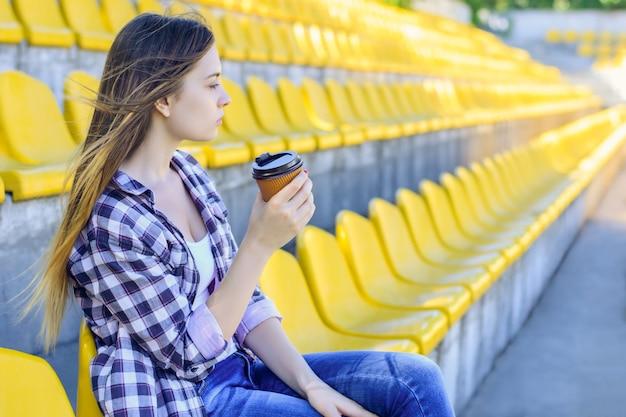 Jonge vrouw in een geruit overhemd met een papieren beker in het stadion zitten