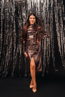Jonge vrouw in een glanzende jurk over zilver klatergoud gordijn