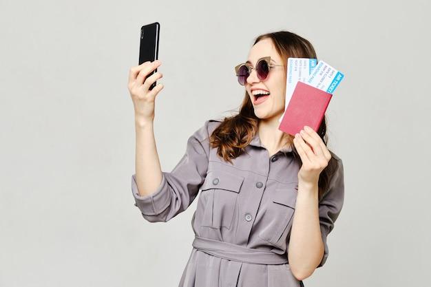 Jonge vrouw in een grijze het vliegtuigkaartjes van de kledingsholding