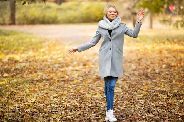 Jonge vrouw in een grijze jas wandelen in het najaar park