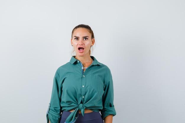 Jonge vrouw in een groen shirt die naar de camera kijkt en zich afvraagt, vooraanzicht.
