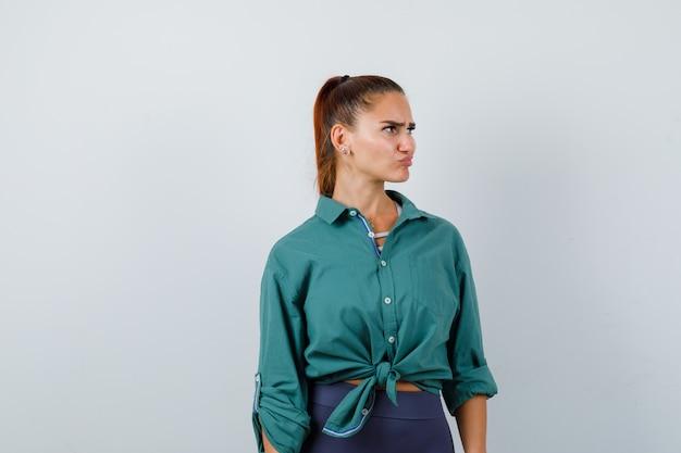 Jonge vrouw in een groen shirt die wegkijkt terwijl ze het gezicht fronst, de lippen buigt en peinzend kijkt, vooraanzicht.