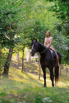 Jonge vrouw in een heldere kleurrijke kleding die een zwart paard berijdt Gratis Foto