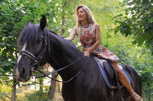 Jonge vrouw in een heldere kleurrijke kleding die een zwart paard berijdt