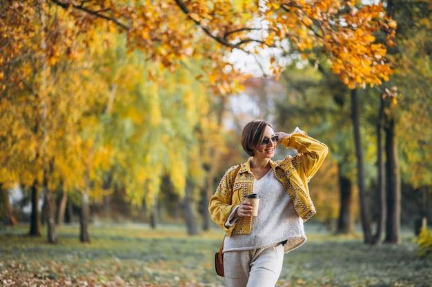 Jonge vrouw in een herfst park koffie drinken