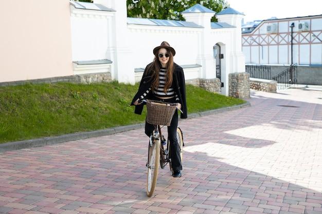 Jonge vrouw in een hoed en bril met een fiets door de stad