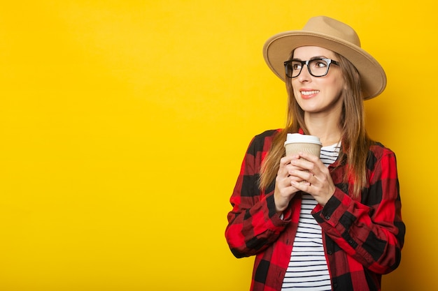Jonge vrouw in een hoed en een geruite hemd houdt een papieren beker met koffie op een gele ondergrond