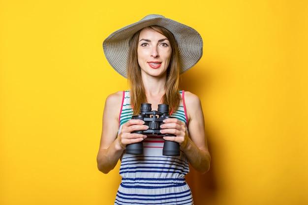 Jonge vrouw in een hoed en een gestreepte jurk houdt een verrekijker op een gele ruimte.