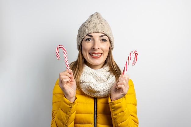 Jonge vrouw in een hoed en jas houdt snoep karamelstokken