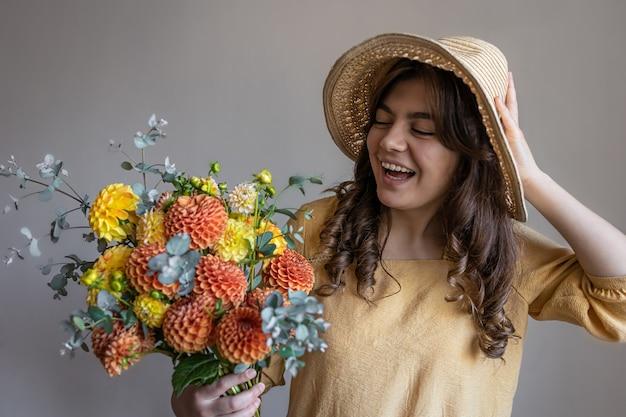 Jonge vrouw in een hoed met een boeket chrysanten op een grijze achtergrond
