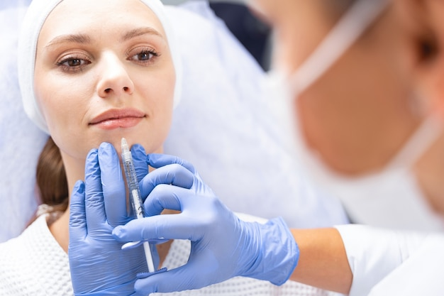 Jonge vrouw in een hoofdband die een hyaluronzuurvullerinjectie in de onderlip krijgt