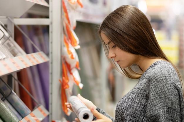 Jonge vrouw in een ijzerhandel kiest behang voor het huis