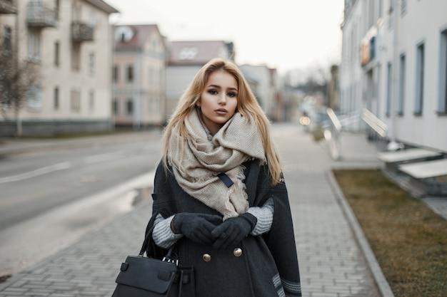 Jonge vrouw in een jas met een sjaal in de stad