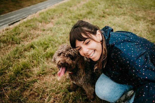 Jonge vrouw in een jasje met een hond