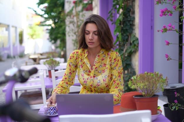 Jonge vrouw in een jurk in een licht straatcafé met een laptop drinkt turkse koffie
