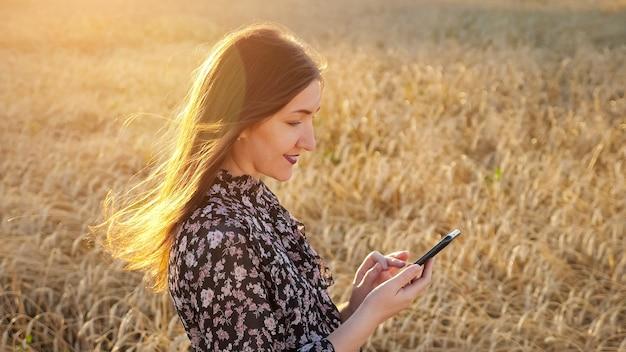 Jonge vrouw in een jurk kijkt naar de telefoon, staat in een tarweveld, zonlicht in haar haar.