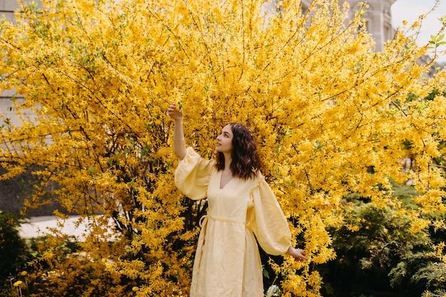 Jonge vrouw in een jurk op een gele struikachtergrond buiten in een tuin