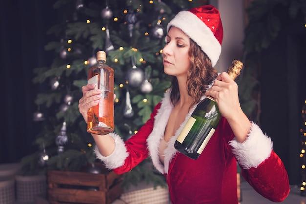 Jonge vrouw in een kerstmankostuum houdt een fles champagne en whisky vast. een alcoholische drank kiezen voor de vakantie.