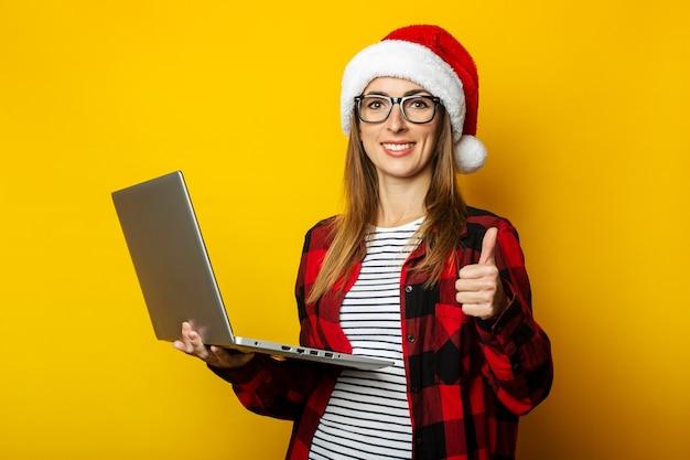 Jonge vrouw in een kerstmuts en een rood shirt in een kooi houdt een laptop