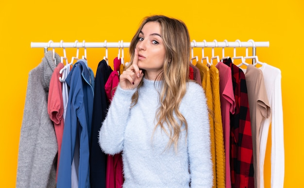 Jonge vrouw in een kledingwinkel die stiltegebaar doet