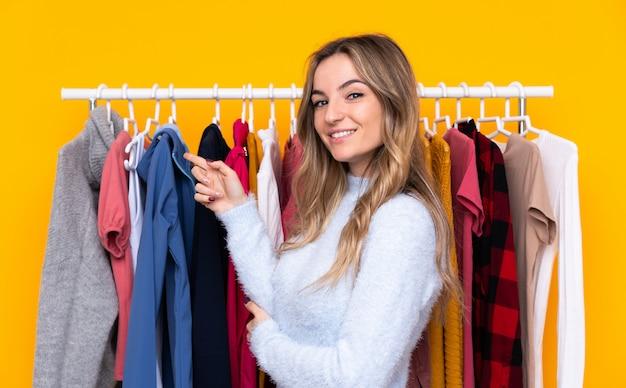 Jonge vrouw in een kledingwinkel over geïsoleerde gele muur wijzende vinger aan de zijkant