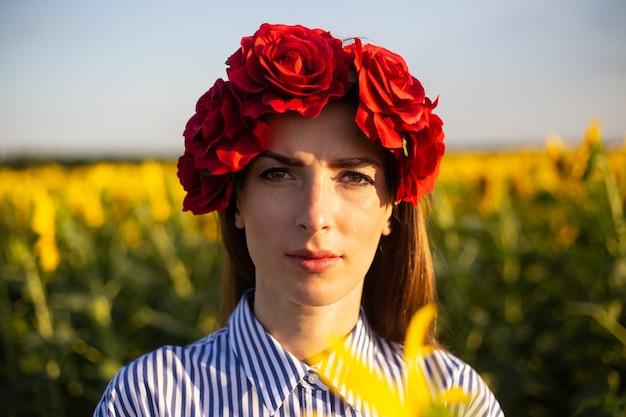 Jonge vrouw in een krans van rode bloemen op een zonnebloemveld bij zonsondergang.