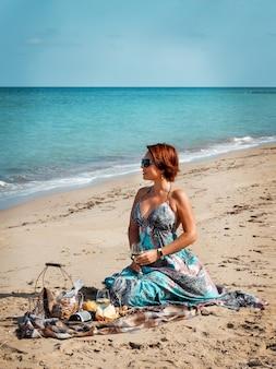 Jonge vrouw in een lange jurk zittend op het strand en wijn drinken