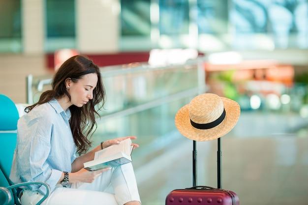 Jonge vrouw in een luchthavenzitkamer die op vluchtvliegtuigen wacht.