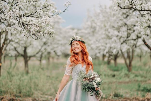 Jonge vrouw in een luxe jurk staat en glimlacht in een bloeiende tuin