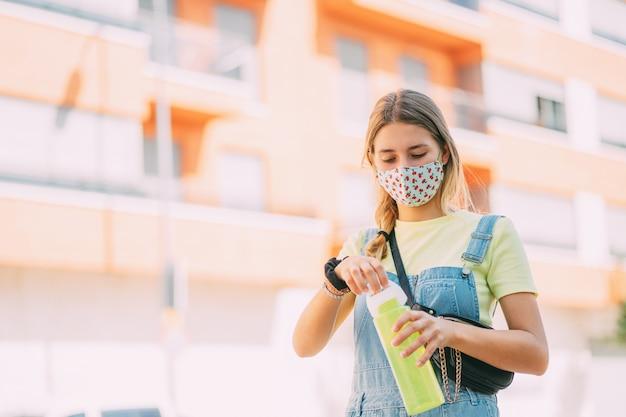 Jonge vrouw in een masker drinkwater en wandelen door de stad. manier van leven, nieuwe normaliteit, covid.