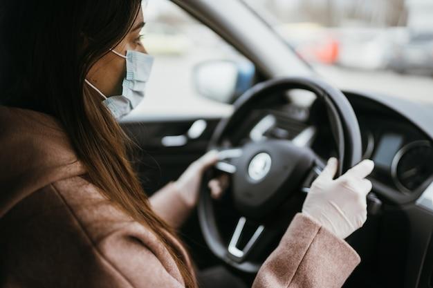 Jonge vrouw in een masker en handschoenen die een auto drijven.