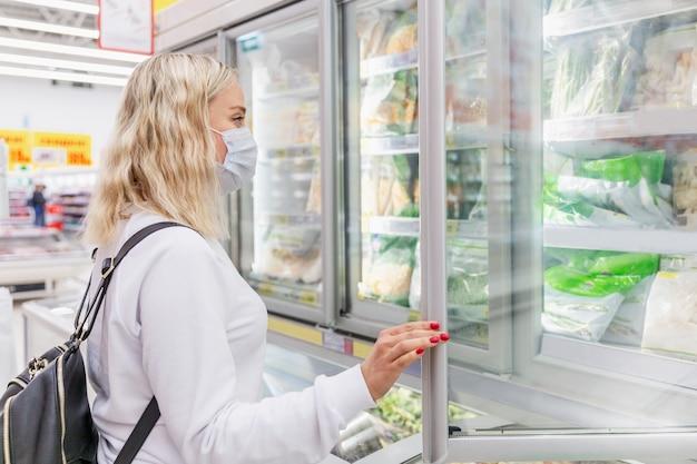 Jonge vrouw in een masker in een supermarkt kiest diepvriesproducten